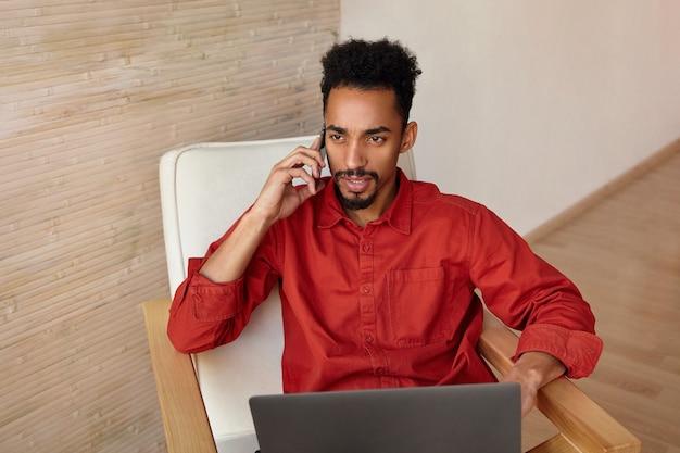 Verbaasd jonge bruinogige donkere man met kort kapsel mobiele telefoon in opgeheven hand houden tijdens het bellen, werken in comfortabele stoel op beige interieur