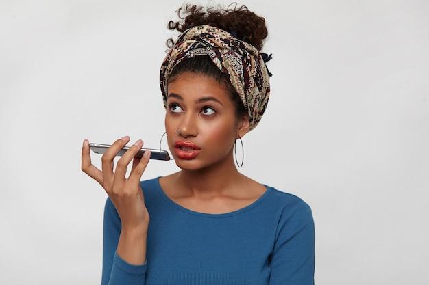 Verbaasd jonge bruinogige krullende brunette vrouw smartphone in opgeheven hand houden terwijl telefoon praten en naar boven kijken, geïsoleerd op witte achtergrond