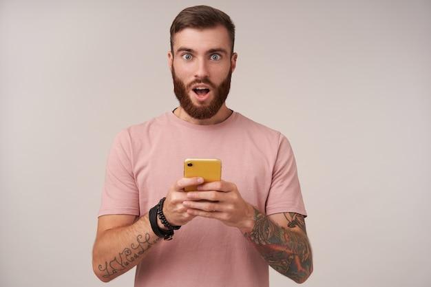 Verbaasd jonge getatoeëerde brunette man met trendy kapsel rond zijn ogen en mond open houden terwijl, beige t-shirt op wit dragen