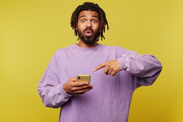 Verbaasd jonge knappe brunette man met donkere huid verrast verrast zijn bruine ogen afronden en tonen op zijn smartphone met opgeheven wijsvinger, poseren op gele achtergrond