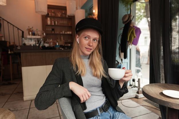 Verbaasd jonge mooie blonde langharige vrouw zittend aan tafel in het stadscafé en het drinken van thee, hoofdtelefoons en trendy warme kleding