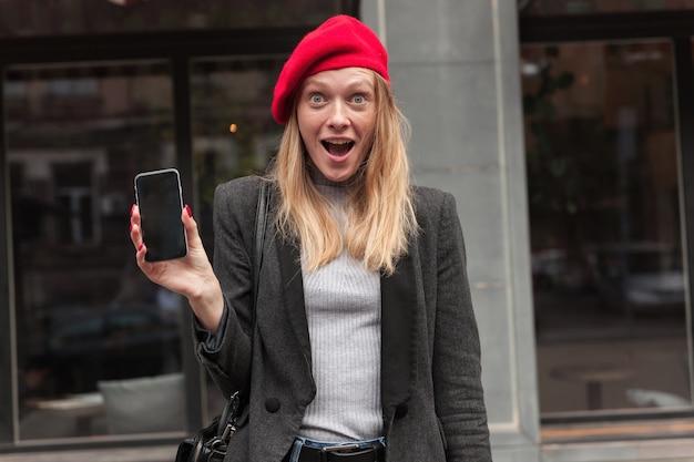 Verbaasd jonge mooie blonde vrouw in elegante kleding rond haar blauwe ogen tijdens het kijken, mond openhouden en wenkbrauwen verbaasd verhogen tijdens buitenwandeling
