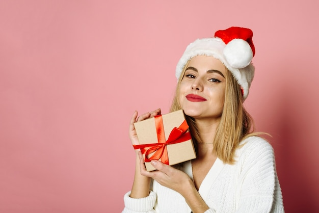 Verbaasd jonge santa vrouw in trui kerstmuts houden cadeau geïsoleerd op roze kleur achtergrond, studio portret. kerstcadeaus concept