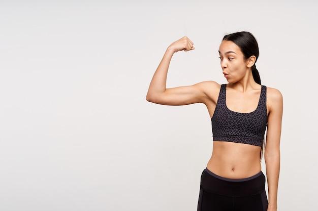 Verbaasd jonge slanke brunette vrouw met paardenstaart kapsel verbaasd op haar biceps kijken terwijl poseren over witte muur in zwarte sportieve beha top en leggins