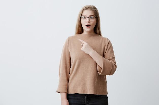 Verbaasd jonge vrouw met blond steil haar, gekleed in bruine trui, wijst naar kopie ruimte met voorvinger adverteert iets, houdt mond wijd open. reclame en verrassingsconcept