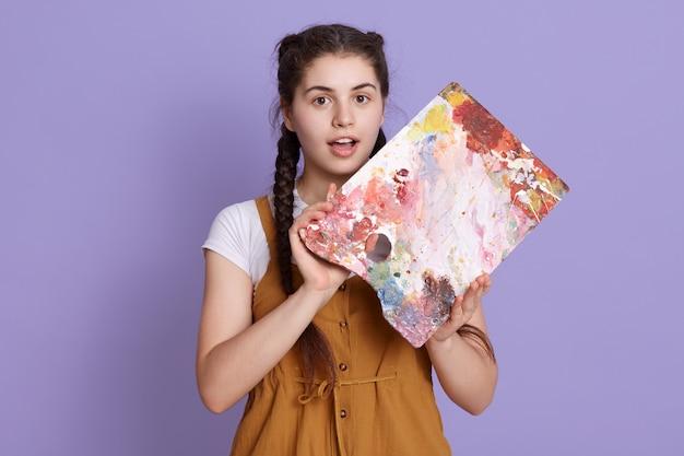Verbaasd jonge vrouw met schilderen palet in handen, houdt de mond open, kijkt verbaasd