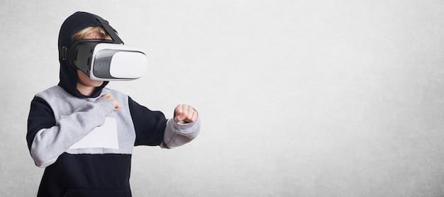 Verbaasd jongetje draagt een virtuele relaity-bril, kijkt films of speelt videogames, gebaart met handen, staat in verdedigingsgebaar