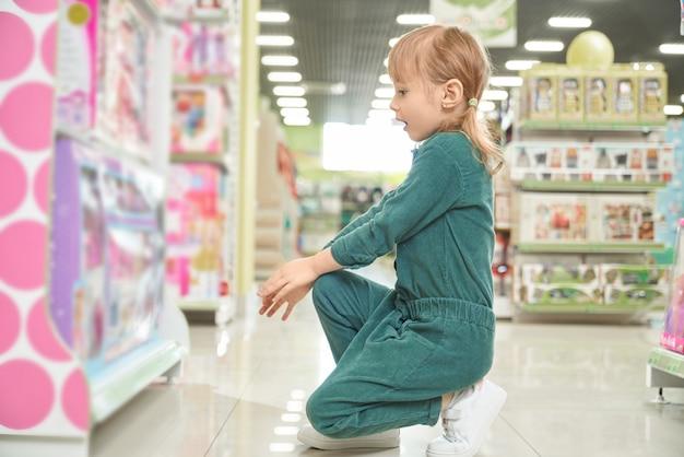 Verbaasd kind zit in de buurt van stands met speelgoed en het kiezen van poppen