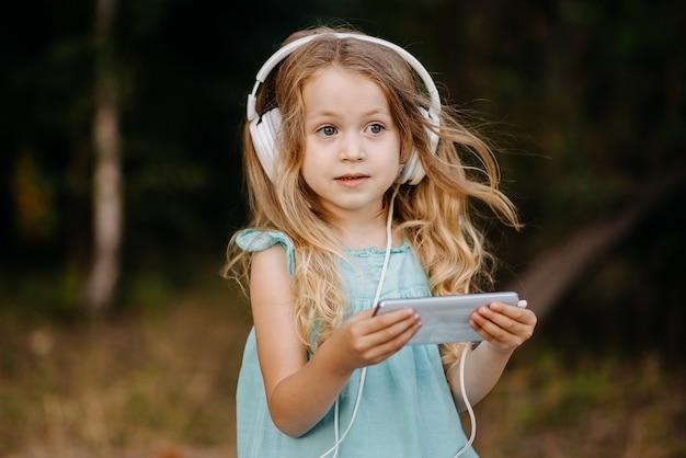 Verbaasd klein kindmeisje met een smartphone in de hand en grote witte koptelefoon kijkt uit