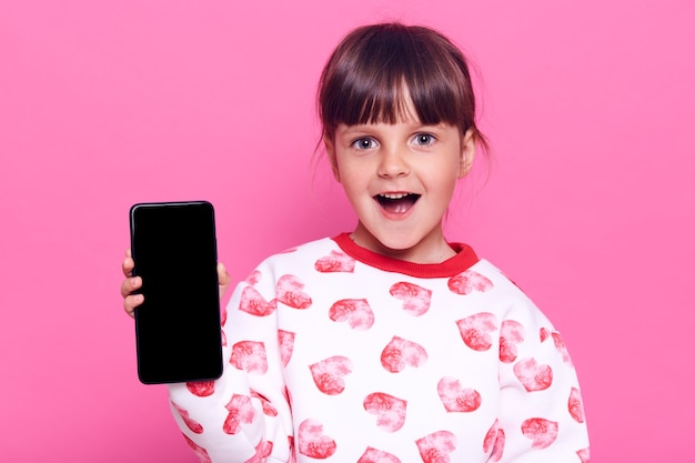 Verbaasd klein meisje met slimme telefoon met leeg scherm met verbaasde gezichtsuitdrukking en geopende mond, poseren geïsoleerd over roze muur.