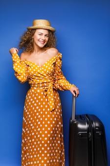 Verbaasd krullend europees meisje poseren voor vakantie met haar bagage