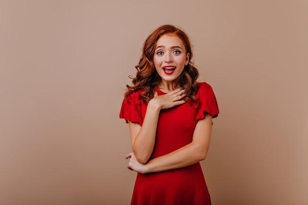 Verbaasd leuk meisje met lang donker haar dat zich op lichte muur bevindt. verfijnde europese vrouw in rode jurk poseren.