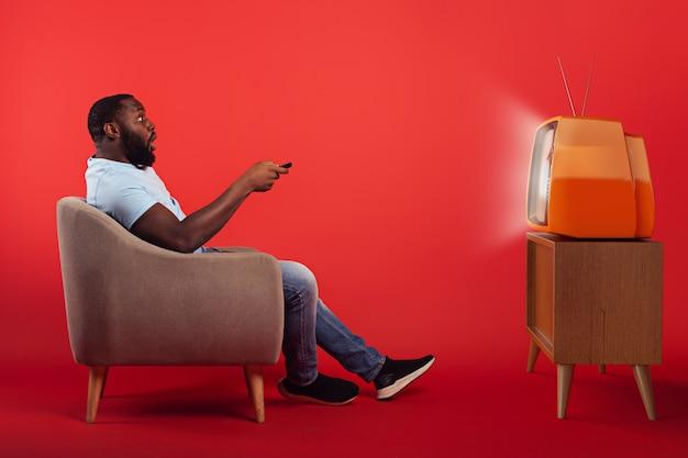 Verbaasd man in de fauteuil kijkt een film op een vintage tv op rode muur