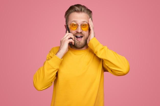 Verbaasd man praten over smartphone in studio