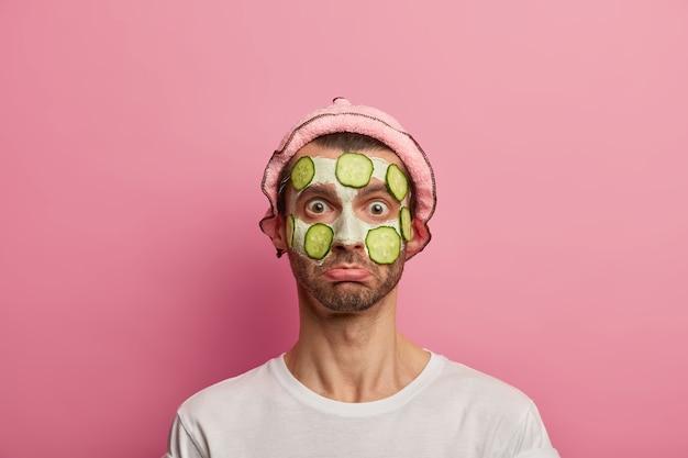 Verbaasd mannelijk model past gezichtsmasker van klei en plakjes komkommer toe om de huid te verjongen, draagt een badmuts, wit t-shirt