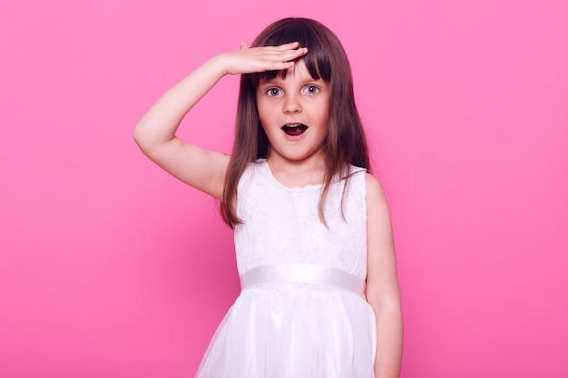 Verbaasd meisje dat een stijlvolle witte jurk draagt die ver weg kijkt met geopende mond en verbaasde uitdrukking, heeft een aangename verrassing, geïsoleerd over roze muur