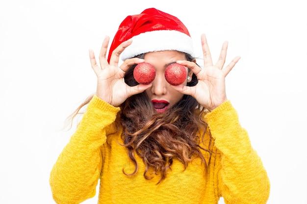Verbaasd meisje die ogen behandelen met kerstmisballen