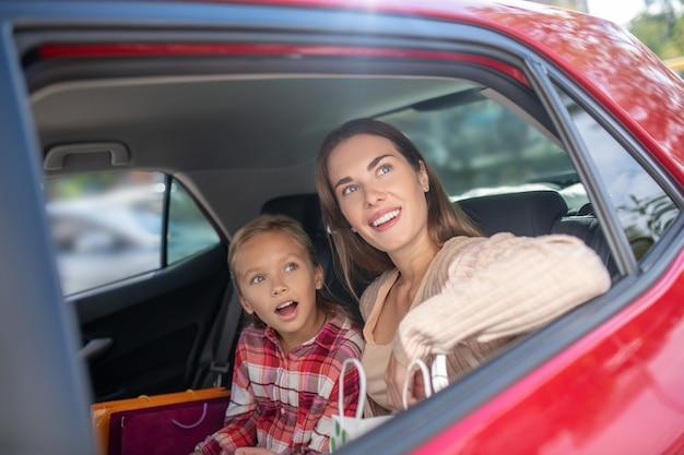 Verbaasd meisje en haar moeder kijken uit het raam op de achterbank van de auto