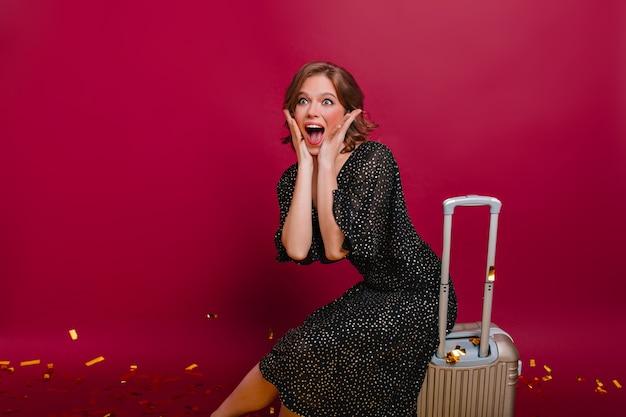 Verbaasd meisje gezicht met handen aan te raken, zittend op een grote koffer