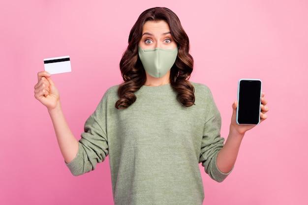 Verbaasd meisje houdt smartphone-debetkaart aan raden gebruik bank online sparen kopersservice in covid quarantaine draag groene trui medische geïsoleerde pastelkleurige achtergrond
