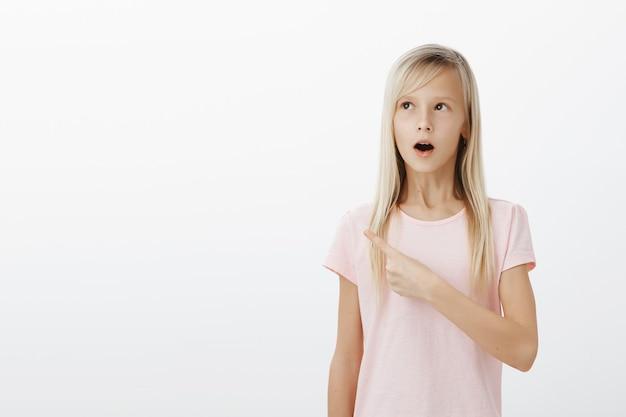 Verbaasd meisje laat haar kaak vallen verbaasd en wijst naar de linker bovenhoek