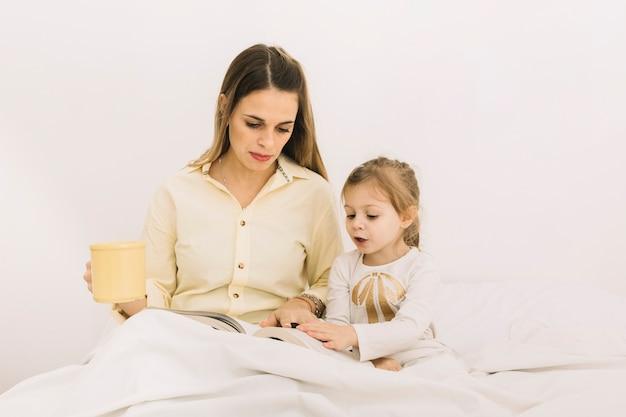 Verbaasd meisje leesboek met moeder in bed