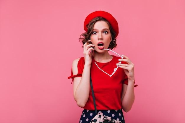 Verbaasd meisje met bruin golvend haar poseren. aantrekkelijke franse jonge dame verrast emoties uitdrukken.