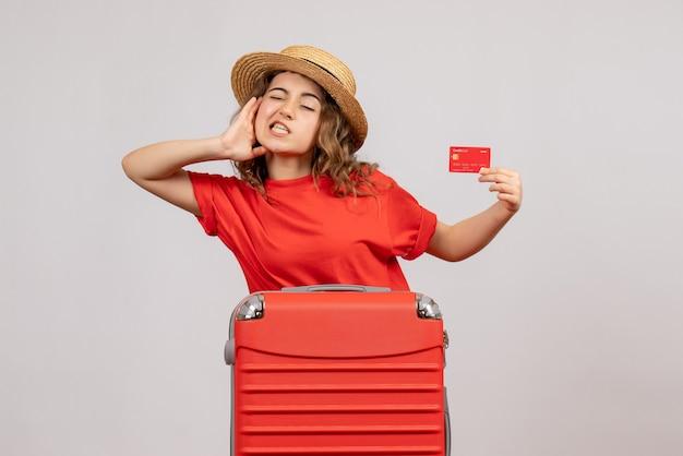 Verbaasd meisje met haar koffer met ticket