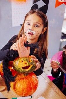 Verbaasd meisje. schattig klein meisje met een geschilderde auto gezicht verbaasd kijken naar enge mooie halloween-decoraties