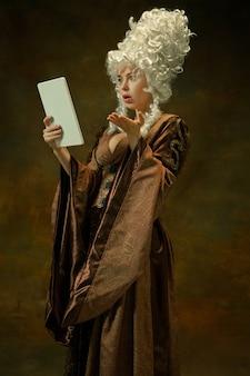 Verbaasd met behulp van tablet. portret van middeleeuwse jonge vrouw in bruine vintage kleding op donkere achtergrond. vrouwelijk model als hertogin, koninklijk persoon. concept vergelijking van tijdperken, modern, mode, schoonheid.