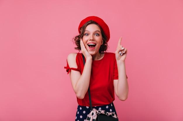Verbaasd mooi meisje met tatoeage die positieve emoties uitdrukt. verfijnde franse dame in baret en rood t-shirt.