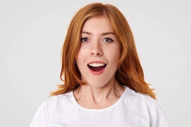 Verbaasd mooi vrouwtje met verbaasde uitdrukking, houdt haar mond open als ze schokken voelt, vertoont witte, zelfs tanden