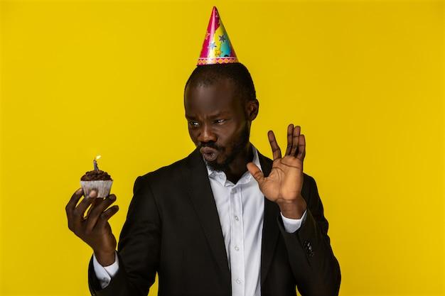 Verbaasd mooie afrikaanse man maakt een wrang gezicht terwijl hij een cake vasthoudt