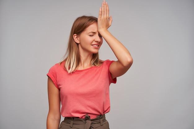 Verbaasd mooie blonde vrouw met natuurlijke make-up palm op haar voorhoofd houden en ogen gesloten houden terwijl poseren op witte achtergrond, gekleed in roze t-shirt