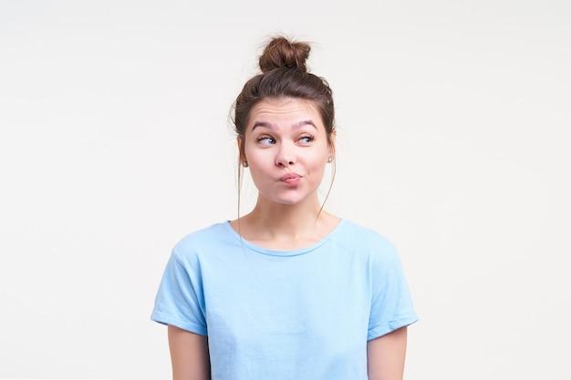 Verbaasd mooie brunette jongedame met natuurlijke make-up haar wenkbrauwen verhogen terwijl ze verwonderd opzij kijken en lippen pruilen, die zich voordeed op witte achtergrond