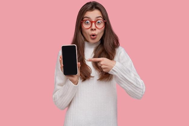 Verbaasd mooie dame wijst naar slimme telefoon met verbaasde blik, toont apparaat, draagt een transparante bril en witte trui