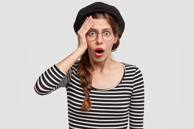 Verbaasd mooie franse vrouw kan haar ogen niet geloven, heeft een doodsbange uitdrukking, opent de mond wijd, gekleed in een gestreepte trui