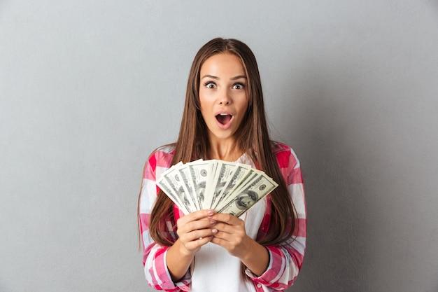 Verbaasd mooie jonge brunette vrouw in geruit hemd aanhouden van geld