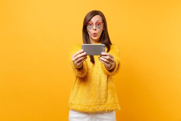 Verbaasd mooie jonge vrouw in bont trui en hart bril doen selfie schot op mobiele telefoon geïsoleerd op heldere gele achtergrond. mensen oprechte emoties, lifestyle concept. reclame gebied.