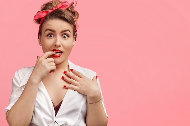 Verbaasd mooie vrouw bijt zenuwachtig vinger, kijkt met verbaasde uitdrukking, krijgt onverwachte rekwisieten, poses