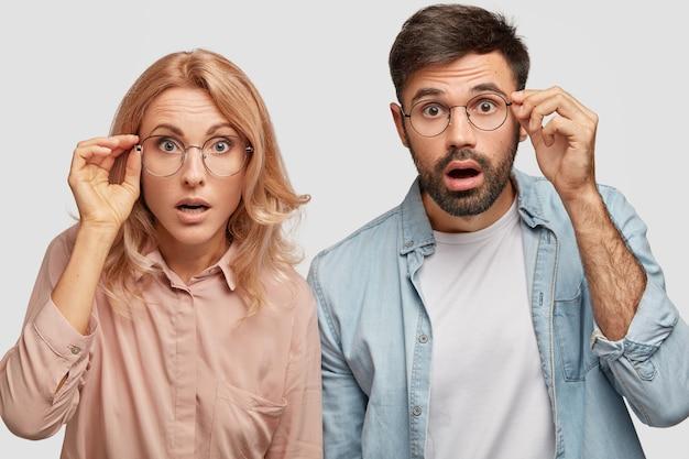Verbaasd mooie vrouw en zijn mannelijke partner, blikken met ogen vol ongeloof, staren door een bril