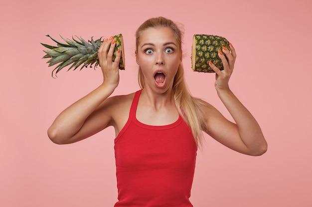 Verbaasd mooie vrouw met blond lang haar met helften ananas bij haar oren, kijkend met grote ogen en mond geopend