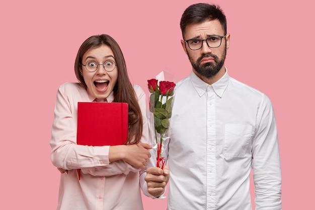 Verbaasd mooie vrouw ontvangt cadeau van mannelijke wonk, draagt rode blocnote, blij bloemen te krijgen. trieste onhandige man heeft eerste date met groepgenoot, presenteert rozen