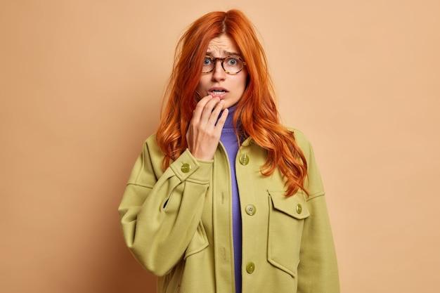 Verbaasd nerveuze europese vrouw met rood haar, afraids van iets, heeft een angstige blik, gekleed in een modieus jasje.