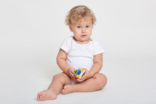 Verbaasd nieuwsgierig kind dat met speelgoed speelt, op de grond zit, blootsvoets is, een bodysuit aankleedt, een baby met golvend haar, poseert tegen een witte muur.