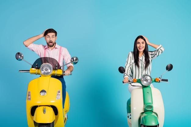 Verbaasd onder de indruk slepen mensen fietsers man vrouw rijden motorfiets aanraking hoofden handen kijken ongelooflijk natuur uitzicht schreeuw wow omg draag formalwear kleding geïsoleerd over blauwe kleur muur
