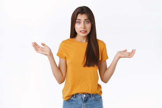 Verbaasd, ongemakkelijk en beschaamd dwaas meisje dat een fout maakt door oeps te zeggen, schouderophalend en handen gespreid vast te houden, kan niet uitleggen hoe de situatie is gebeurd, glimlachend bezorgd, staande witte achtergrond