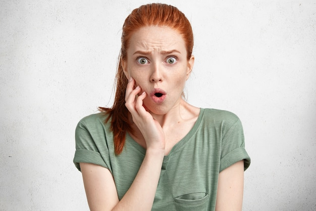 Verbaasd ontevreden mooie jonge vrouw met rood haar vastgebonden in paardenstaart, houdt mond rond, kijkt met geschokte uitdrukking en luistert naar negatief nieuws