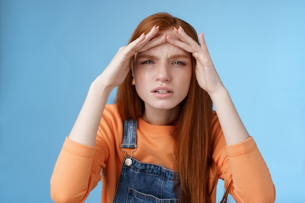 Verbaasd onzeker schattig grappig roodharige europese vrouw zoekt iemand loensend kan niet zien zonder bril turen in de verte handen vasthouden voorhoofd bedekken zicht zonlicht staand blauwe achtergrond