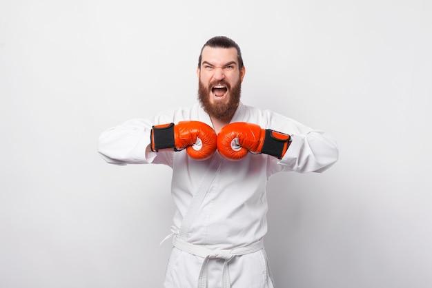 Verbaasd opgewonden bebaarde man in taekwondo dobok vieren over witte muur